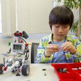 教材説明。レゴマインドストームの組み立てをしている小学生