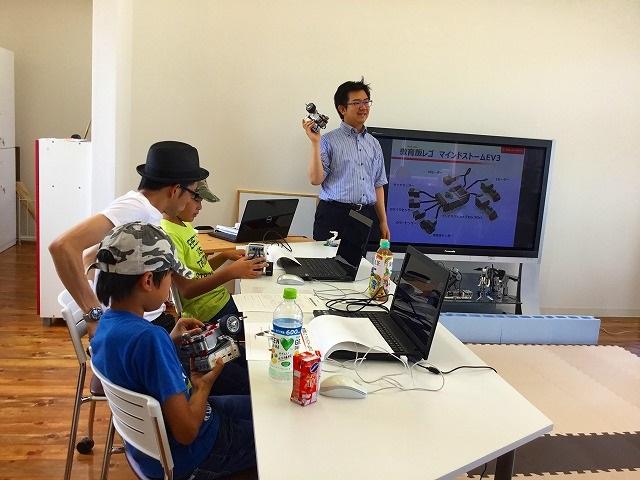 ロボットプログラミング教室、体験会の様子。説明をする先生と聞く生徒